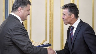 """RESTRICTED TO EDITORIAL USE - MANDATORY CREDIT """"AFP PHOTO / PRESIDENTIAL PRESS-SERVICE / ANDREW KRAVCHENKO"""" - NO MARKETING NO ADVERTISING CAMPAIGNS - DISTRIBUTED AS A SERVICE TO CLIENTS This handout picture taken and released by Presidential press-service on August 7, 2014 shows Ukrainian President Petro Poroshenko (L) awarding NATO Secretary General Anders Fogh Rasmussen with the highest award for foreigners in Ukraine - Order of Freedom prior to their talks in Kiev. Rasmussen was awarded """"for his significant contribution to the development of cooperation between the Ukrainian state and the Atlantic Alliance, strong support in defending the sovereignty, independence and integrity of Ukraine."""" The visit, at the invitation of Poroshenko, is intended to discuss an upcoming meeting on NATO-Ukraine partnership. AFP PHOTO/ PRESIDENTIAL PRESS-SERVICE/ MYKOLA LAZARENKO"""