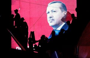 Turkish Supporters are silhouetted against a screan showing President Tayyip Erdogan during</div>                         <div class=