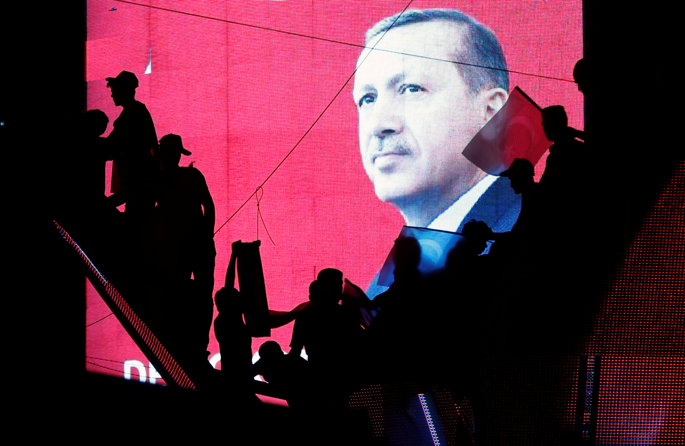 Turkish Supporters are silhouetted against a screan showing President Tayyip Erdogan during a pro-government demonstration in Ankara, Turkey, July 17, 2016. REUTERS/Baz Ratner